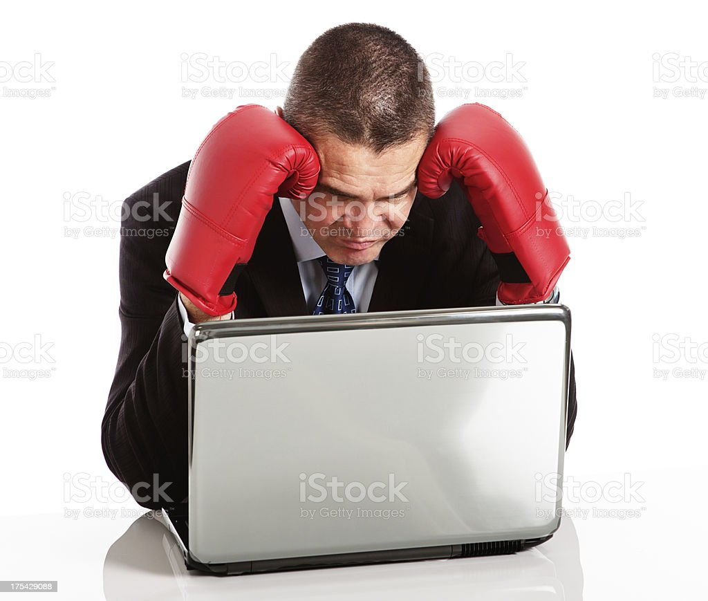 Bored businessman in boxing gloves is frustrated by laptop stock photo