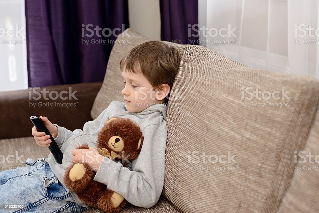 Bored child sitting on the sofa and watching tv. stock photo