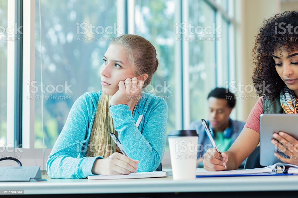 Bored college student daydreams in class stock photo