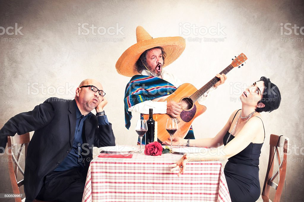 bored couple at dinner oblyed to listen to a mexican musician stock photo