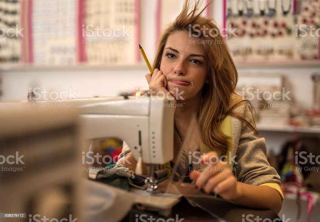 Bored female tailor in a clothing design studio. stock photo