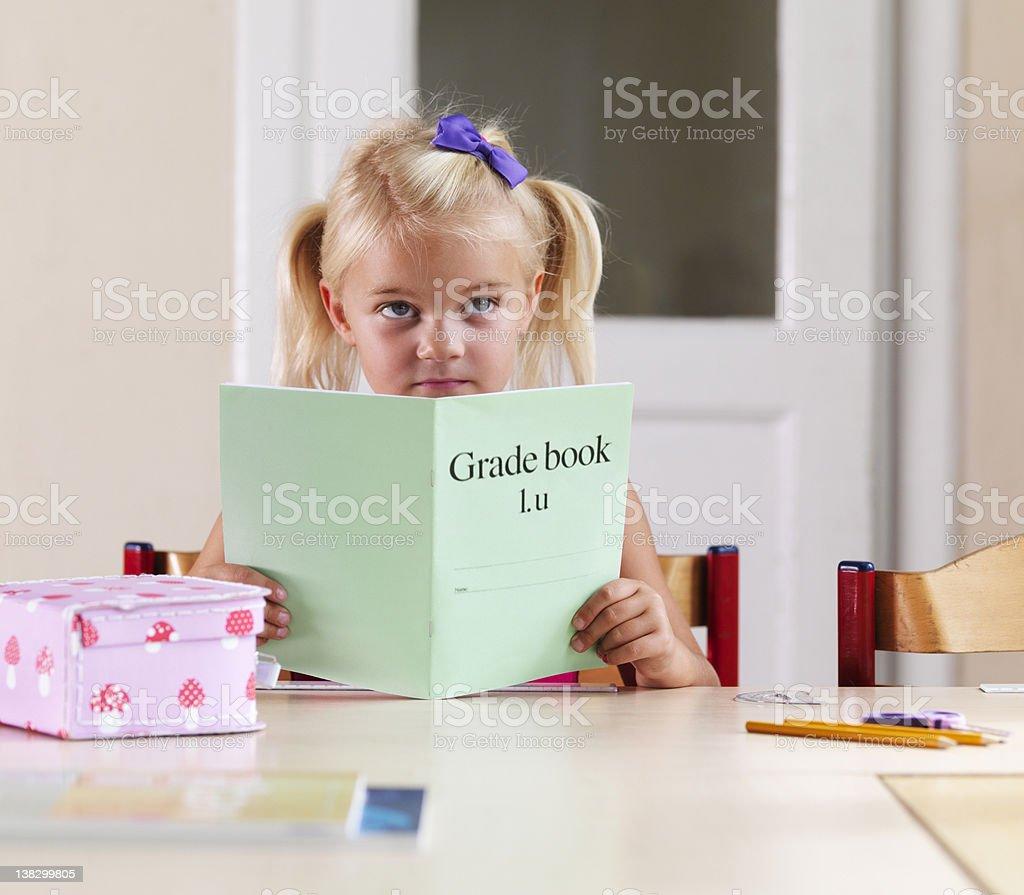 Bored girl doing homework at desk stock photo