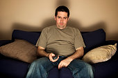 Bored, lazy, overweight man sits on the sofa