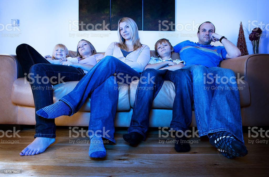 Bored, listless faces on a family watching TV royalty-free stock photo