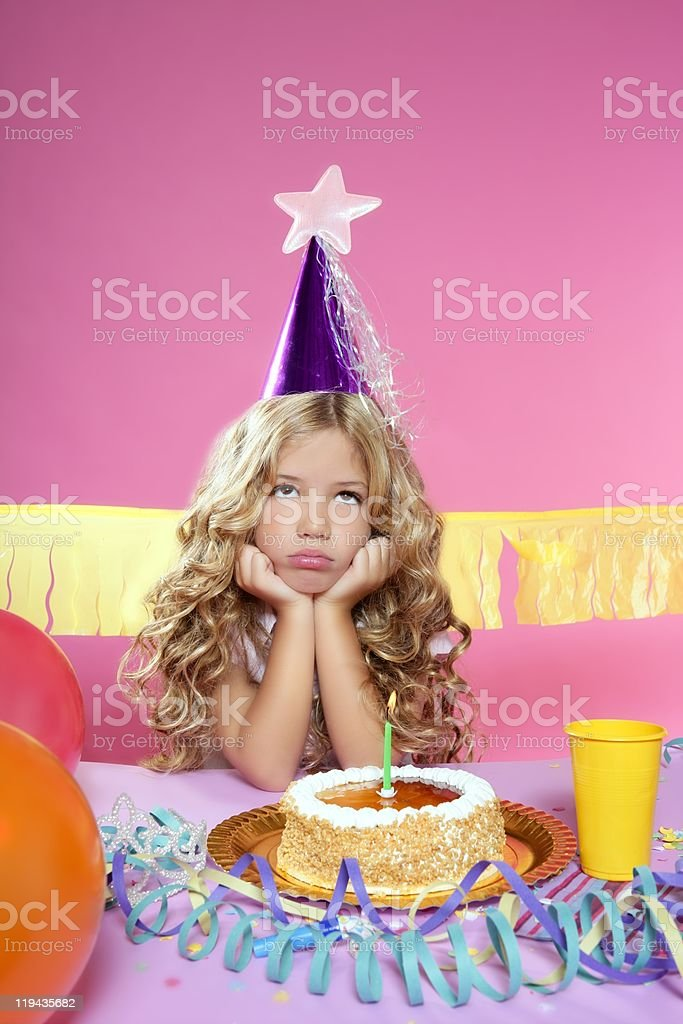 bored little blond girl in birthday party candle cake royalty-free stock photo