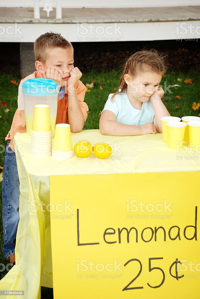 Bored Little Boy and Girl Standing Behind Lemonade Stand royalty-free stock photo