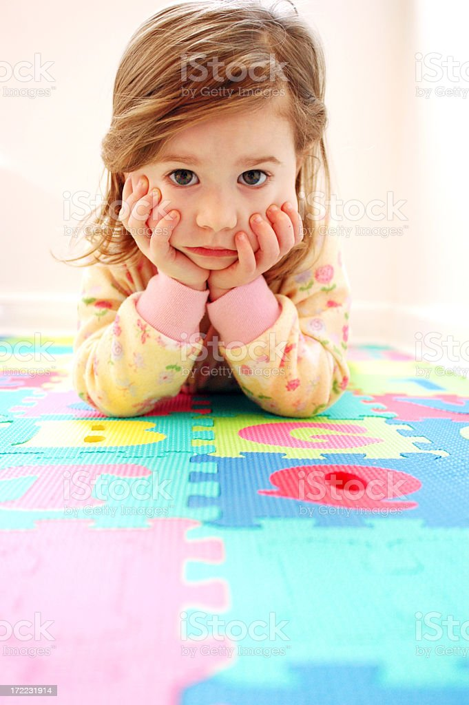 Bored Little Girl Lying on Floor Looking at Camera royalty-free stock photo