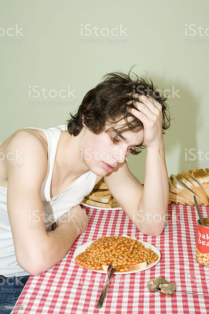 Bored looking student with a plate of beans stock photo