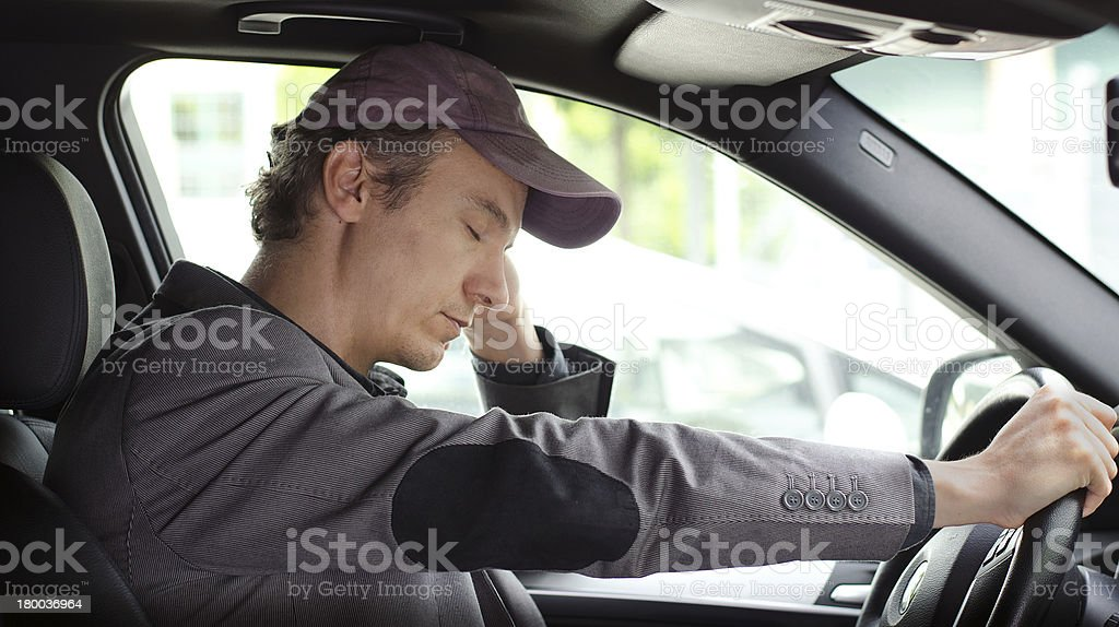 Bored man at the wheel of his car sleeping stock photo