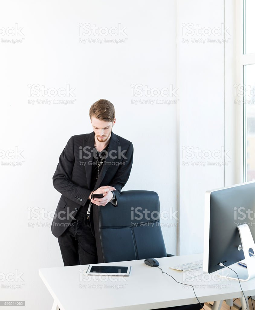 Bored Office Worker Checking Social Media On Smartphone stock photo