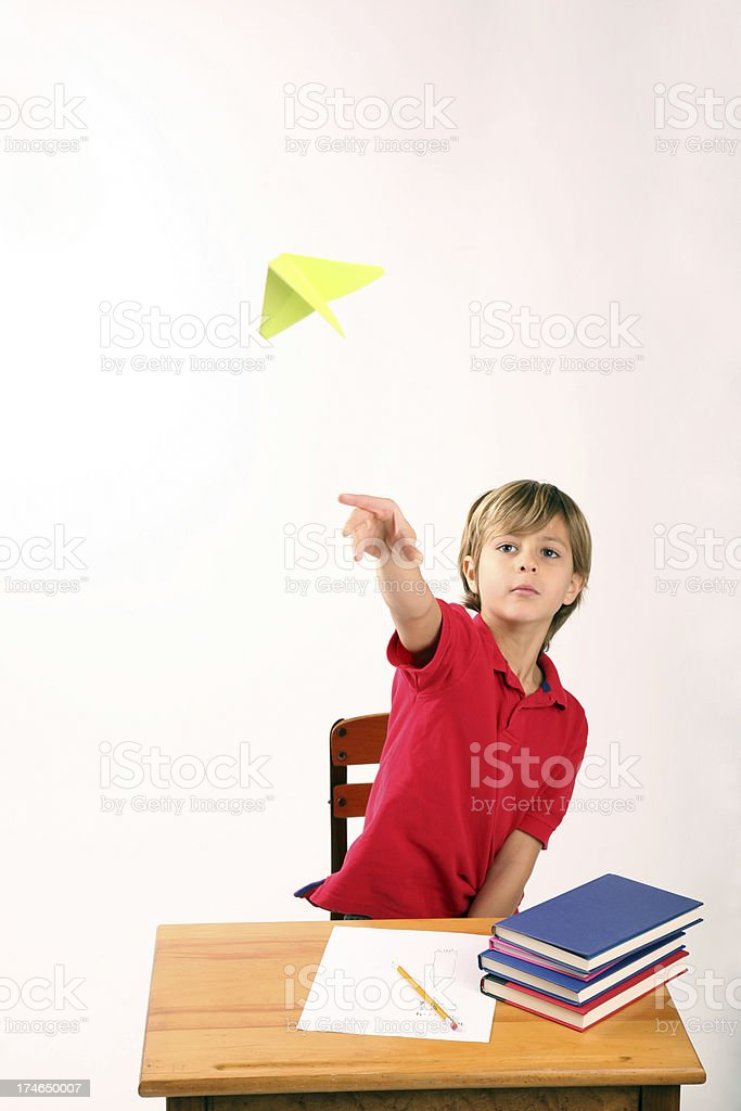 Bored Rebellious Student Flying Paper Airplane in School stock photo