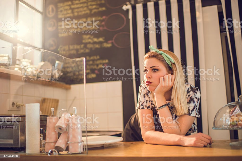 Bored retro styled female worker waiting for her customers. stock photo