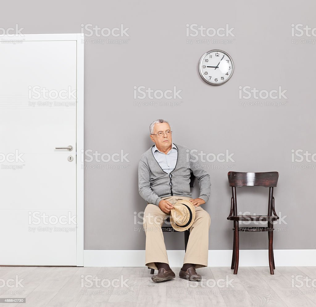Bored senior gentleman sitting in an office lobby stock photo