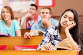 Bored Student At Desk With Classmates In Background