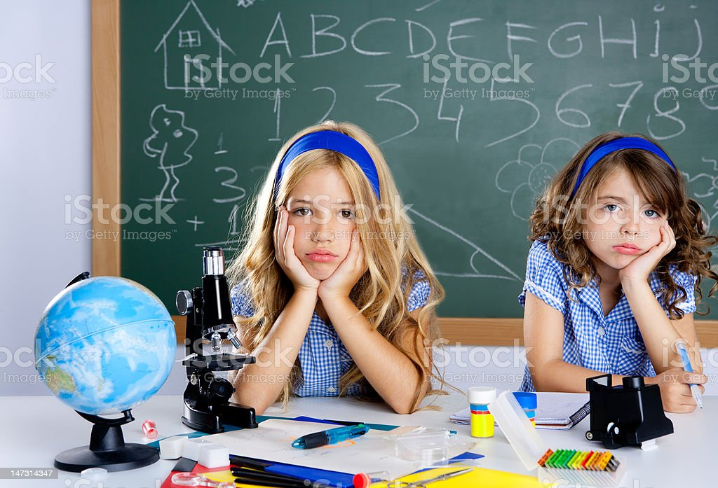Bored student kids at school classroom in desk royalty-free stock photo
