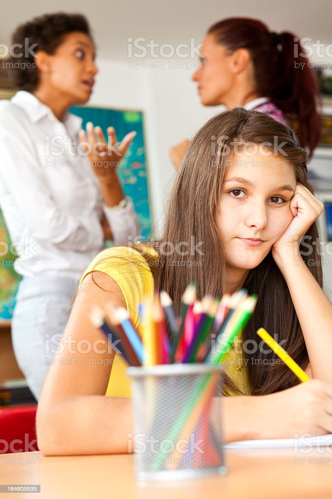 Bored or depressed student looking at camera while teacher and parent...