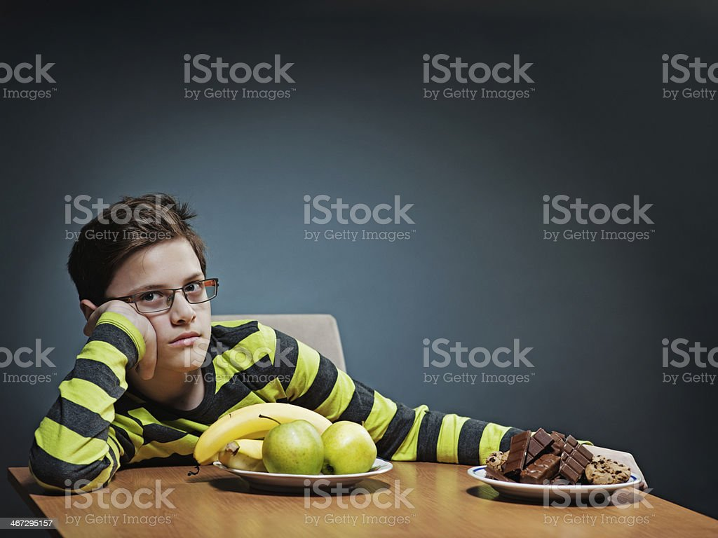 Annoiato adolescente scegliendo tra frutta e dolci. foto stock royalty-free