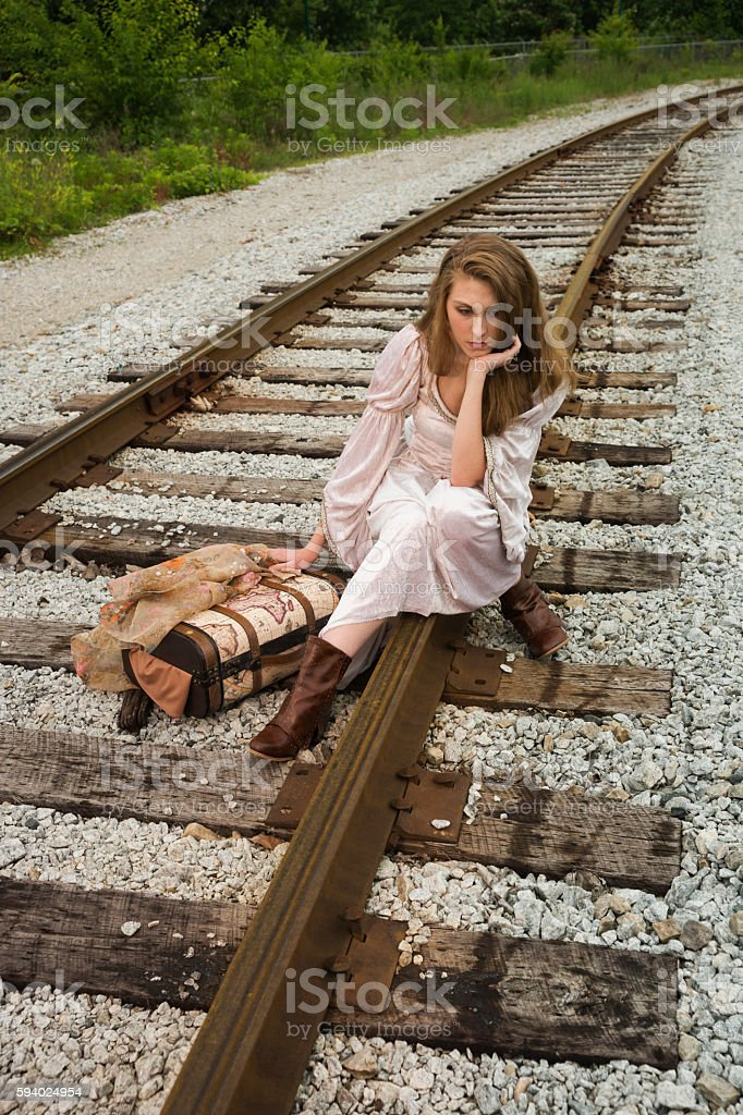 Bored tired woman rests on railroad tracks stock photo
