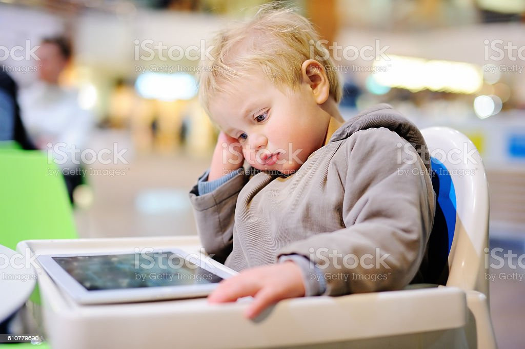 Bored toddler with a digital tablet stock photo