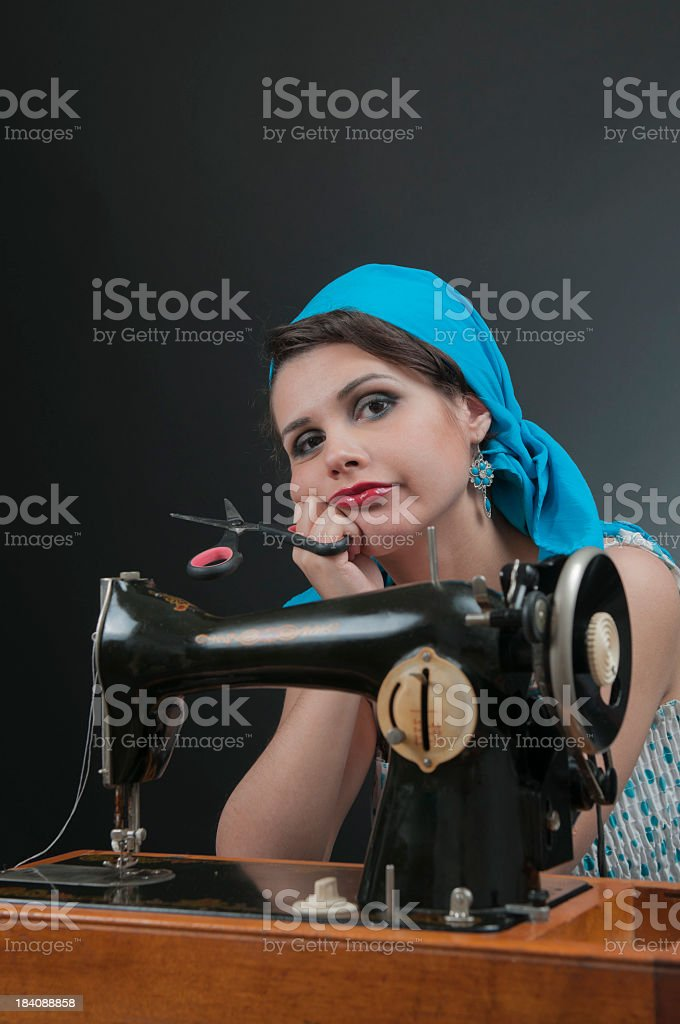 Bored woman with old sewing machine, looking at the camera royalty-free stock photo