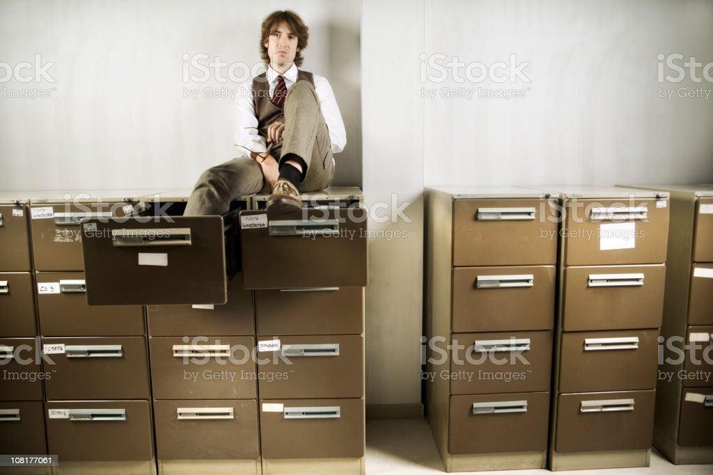 Bored Young Businessman Sitting on Filing Cabinets royalty-free stock photo