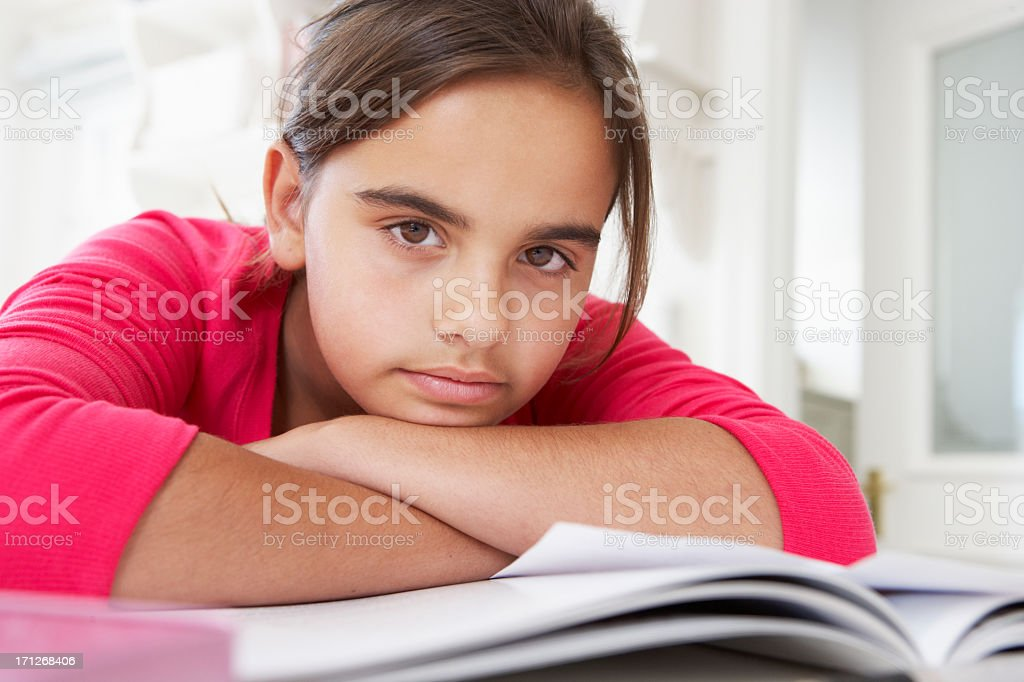 Bored Young Girl Doing Homework At Desk In Bedroom stock photo