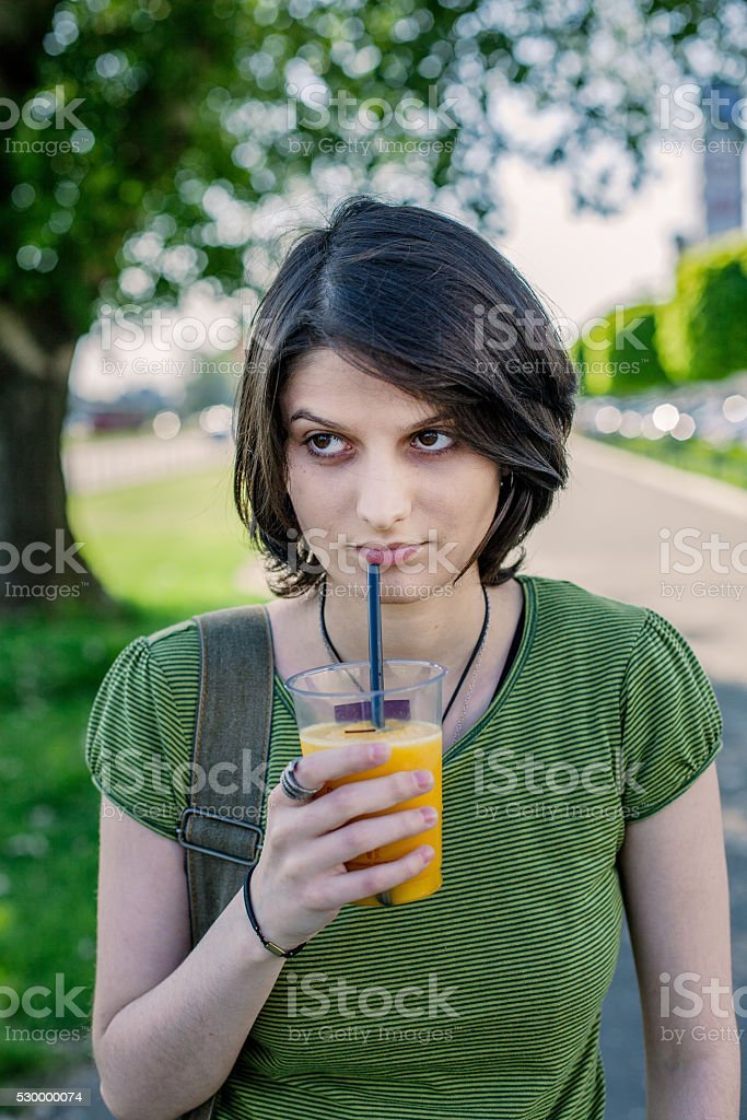 Bored young girl drinking orange smoothie royalty-free stock photo