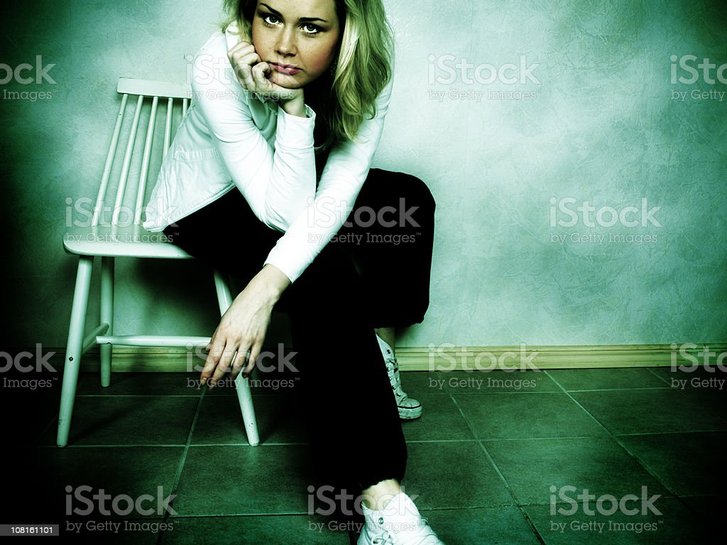 Bored Young Woman Sitting in Chair royalty-free stock photo