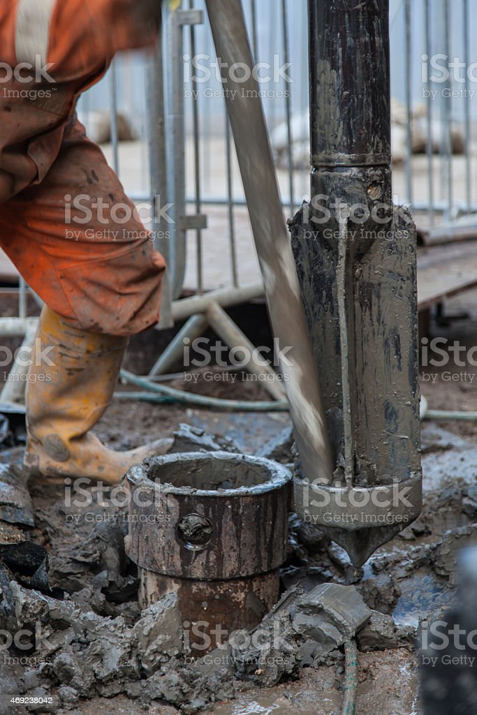 Borehole for soil testing drill bit being cleared of clay stock photo