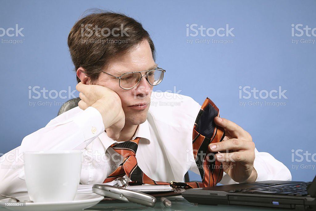 Boring Businessman playing with his necktie stock photo
