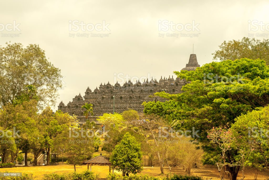 Borobudur from a distance framed by trees stock photo