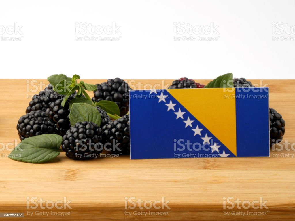 Bosnia and Herzegovina flag on a wooden panel with blackberries isolated on a white background stock photo