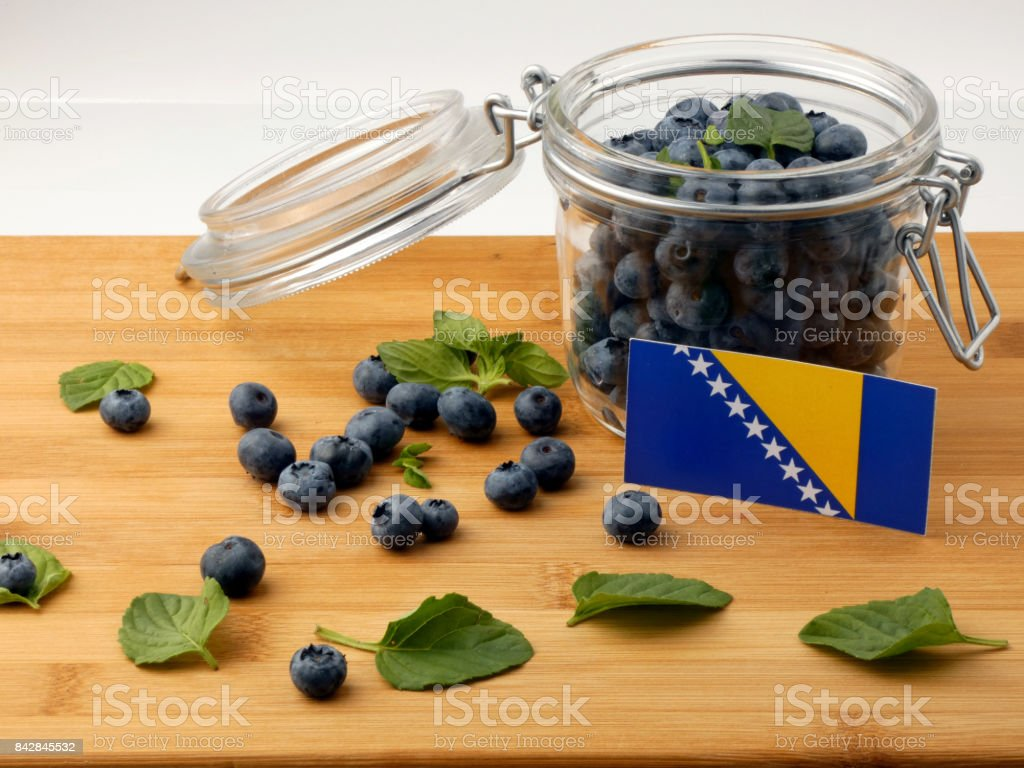 Bosnia and Herzegovina flag on a wooden plank with blueberries isolated on white stock photo