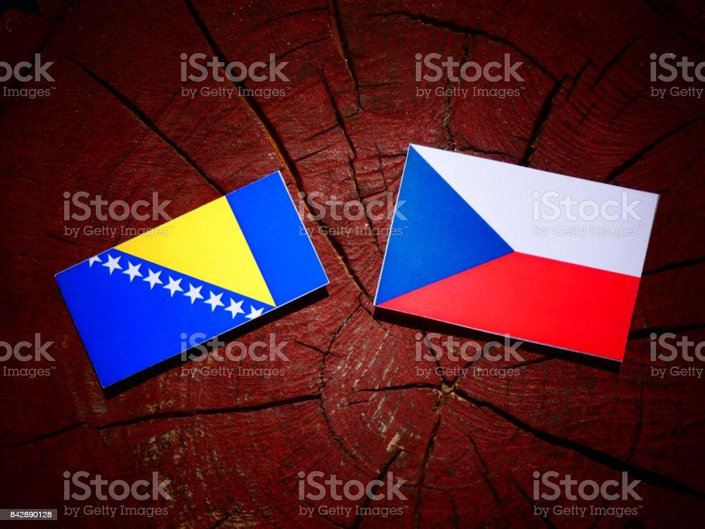 Bosnia and Herzegovina flag with Czech flag on a tree stump isolated stock photo