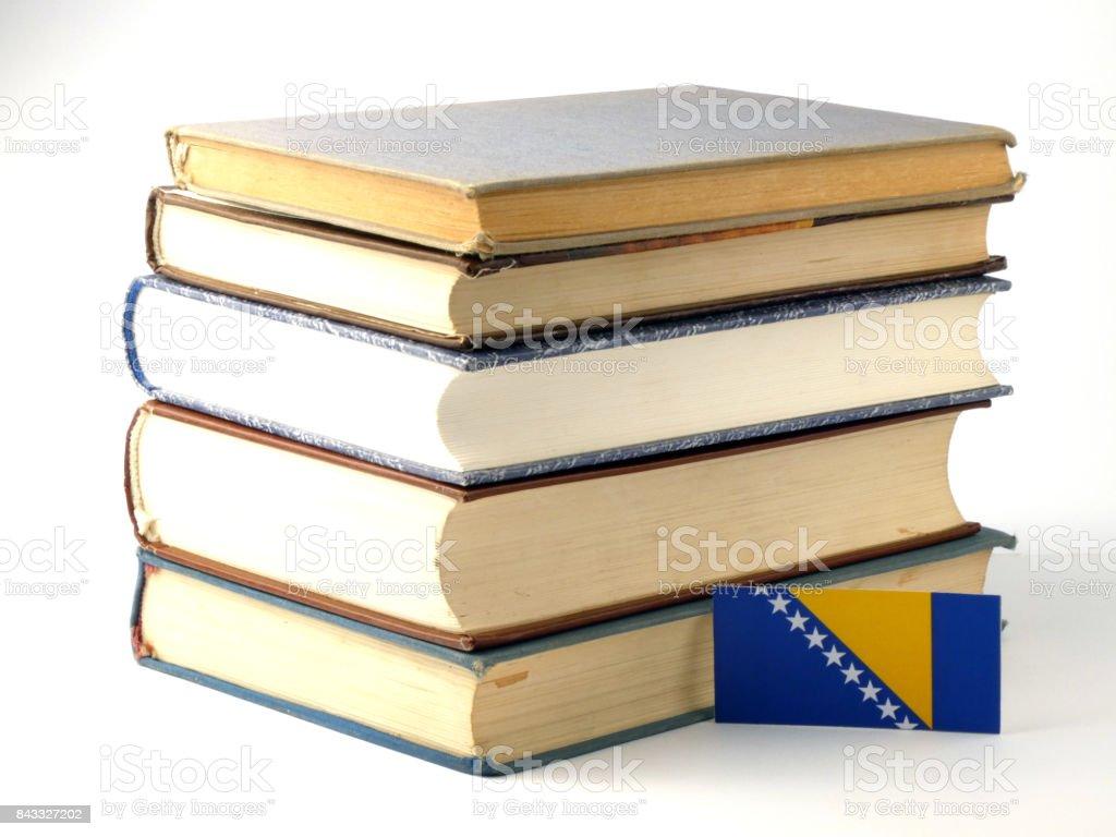 Bosnia and Herzegovina flag with pile of books isolated on white background stock photo