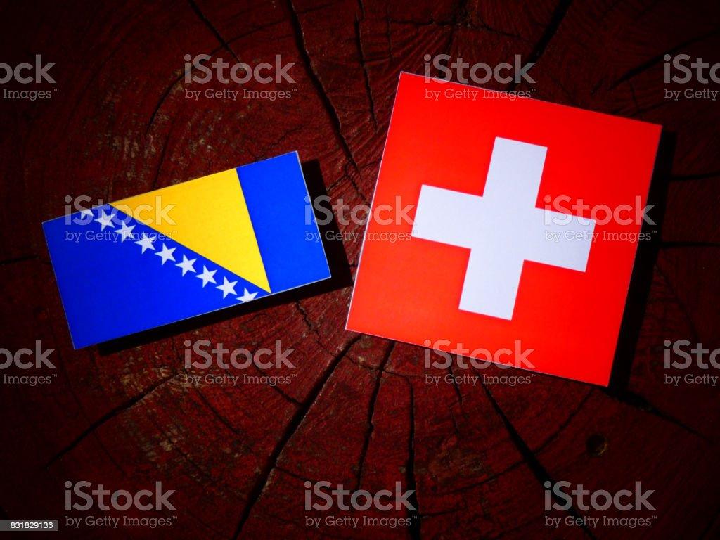 Bosnia and Herzegovina flag with Swiss flag on a tree stump isolated stock photo