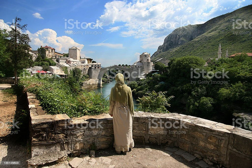 Bosnian girl looking at famous old Mostar bridge...Bosnia and Herzegovina stock photo