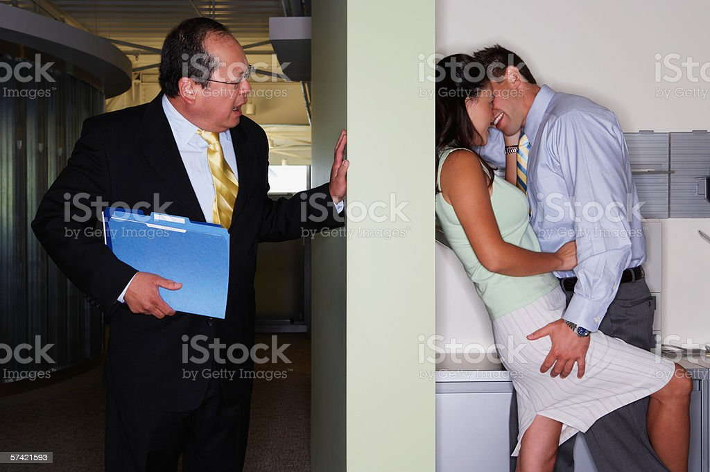 Boss catches colleagues kissing royalty-free stock photo