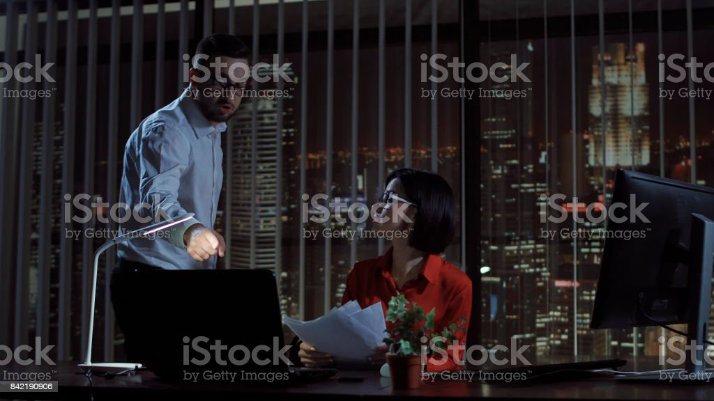 Boss creaming on woman in office stock photo