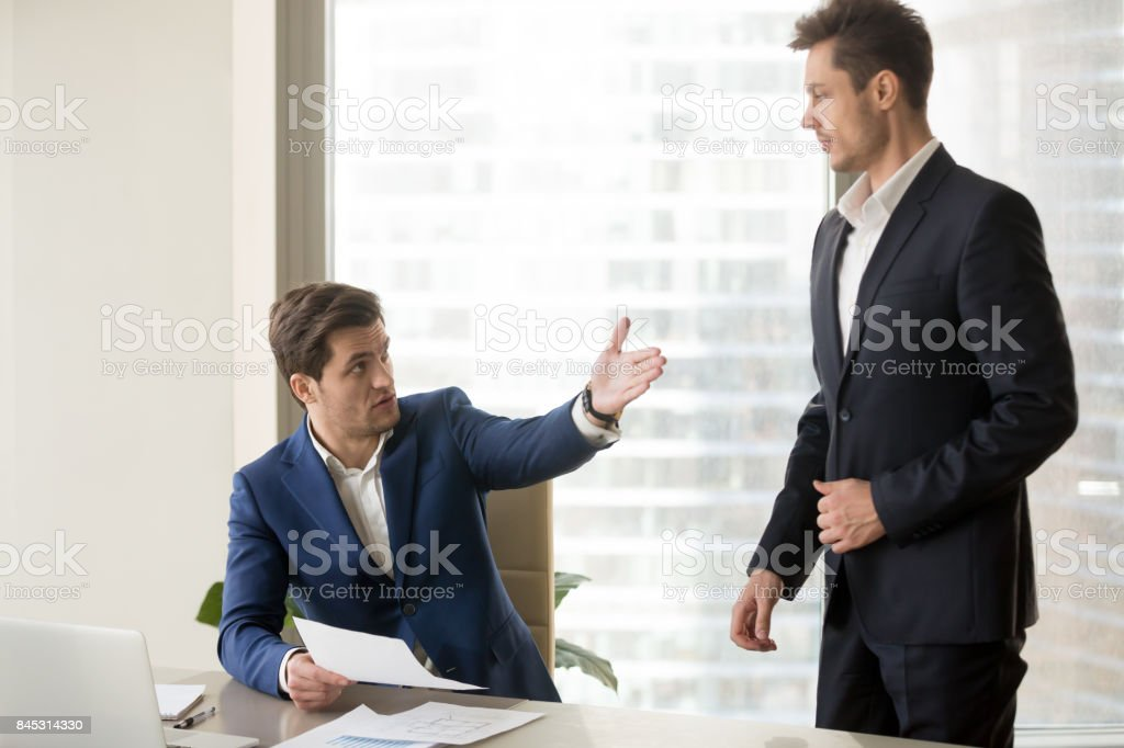 Boss criticizing and firing employee for bad work stock photo