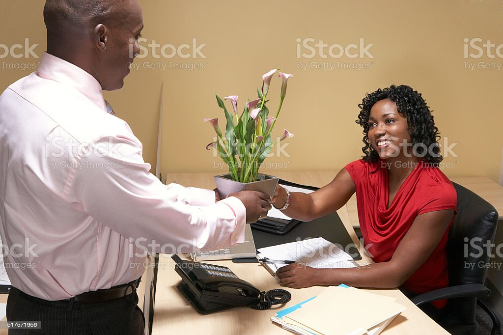 Boss giving his administrative assistant flowers stock photo