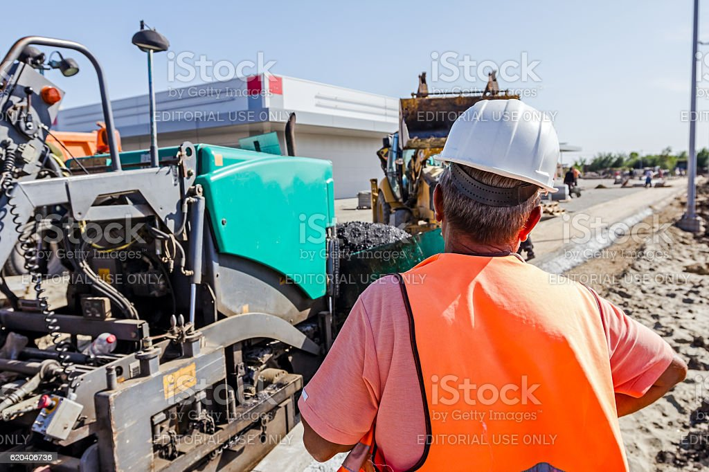 Boss is control workers on construction site. Transport hot asph stock photo