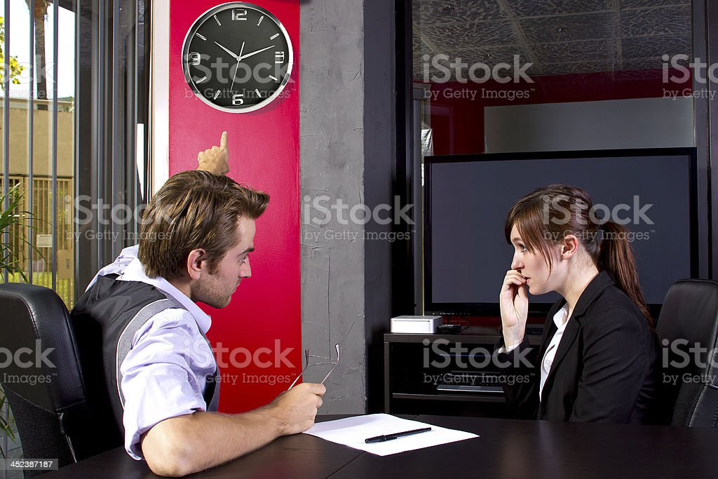 A boss reminding an employee that she is late stock photo