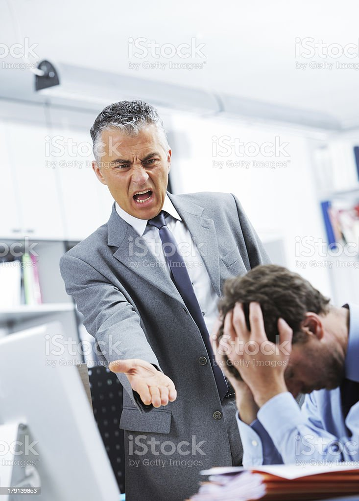 Boss reprimanding employee while he hides behind his hands royalty-free stock photo