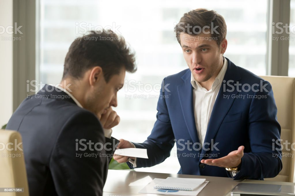 Boss yelling at employee for missing deadline, bad work results stock photo