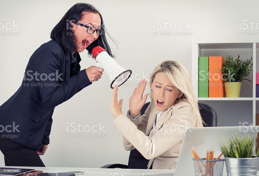 Boss yelling at employee on megaphone stock photo