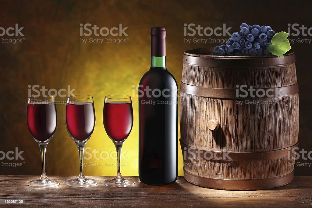 Bottle and a glass of wine with wooden barrel. royalty-free stock photo