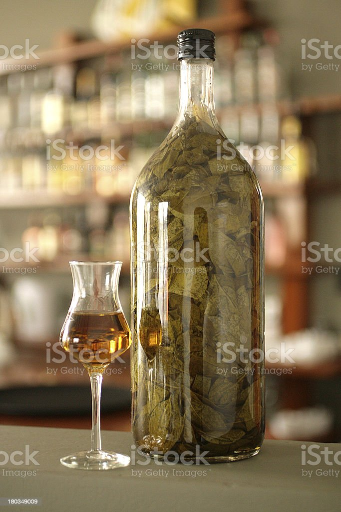 Bottle and cup of coca leaves macerated in peruvian pisco stock photo