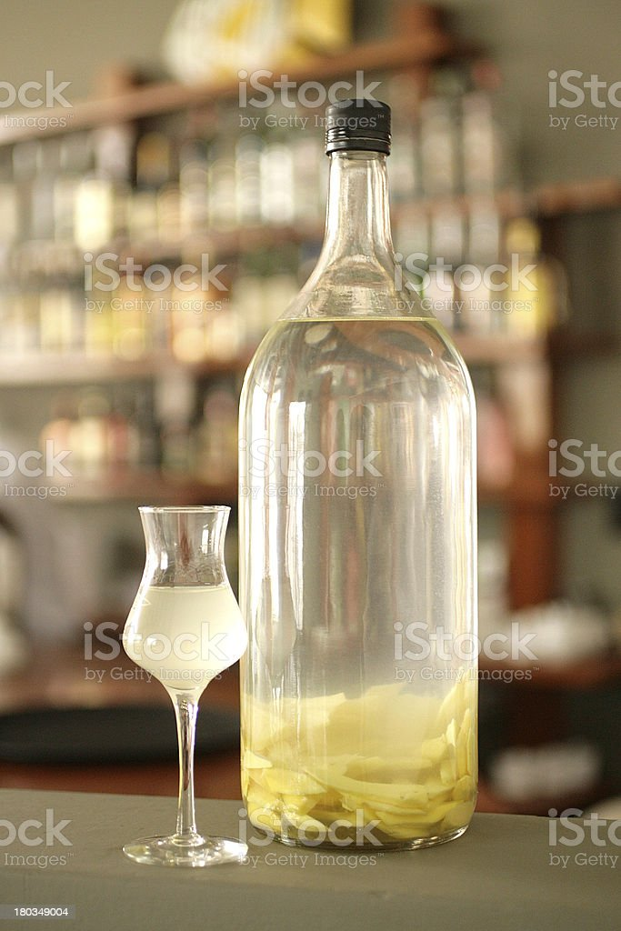 Bottle and cup of ginger slices macerated in peruvian pisco stock photo