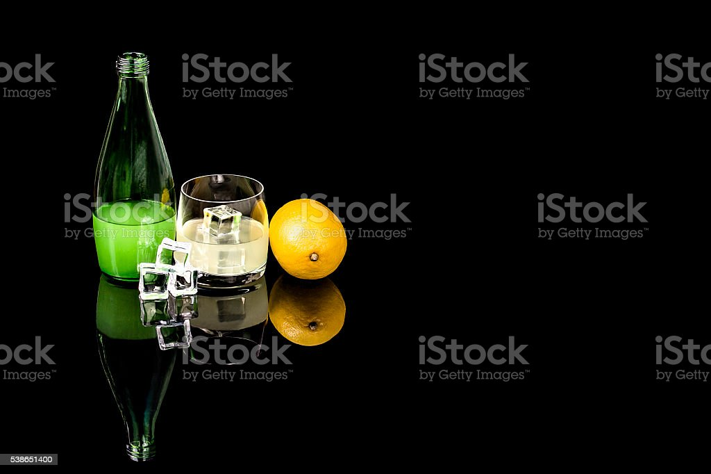 Bottle and glass beverage with ice and lemon on black background stock photo